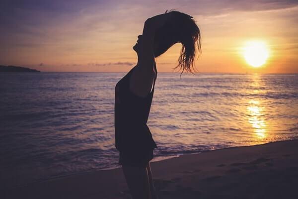 海辺で髪全体をかきあげる女性