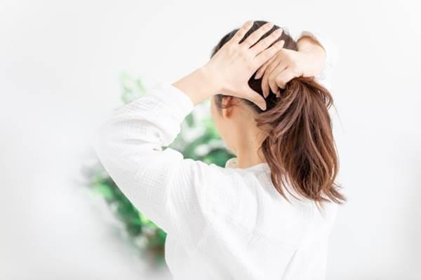 髪の毛を束ねる女性