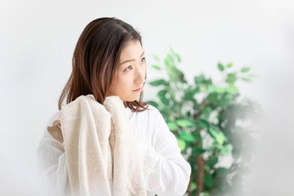 髪の毛をタオルで拭く女性