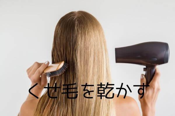 くせ毛をドライヤーで乾かしている女性